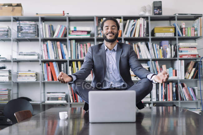 Young businessman sitting in office meditating in front of laptop — Stock Photo