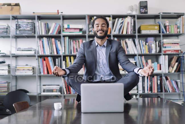 Jungunternehmer sitzt im Büro und meditiert vor Laptop — Stockfoto