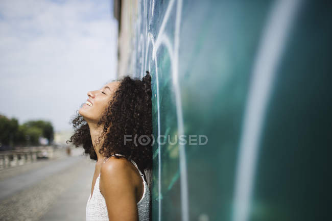 Woman leaning against wall — Stock Photo