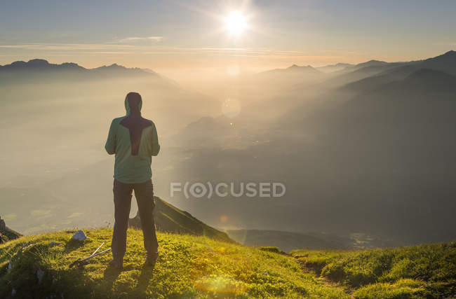 Hiker looking at distance at sunrise — Stock Photo