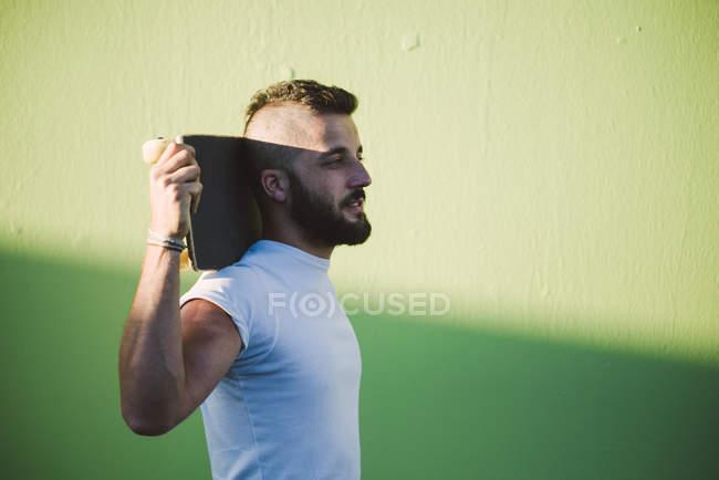 Homme avec planche à roulettes sur les épaules, debout devant le mur vert — Photo de stock