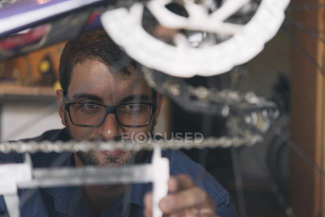 Mechanic in repair shop repairing bicycle, closeup view — Stock Photo
