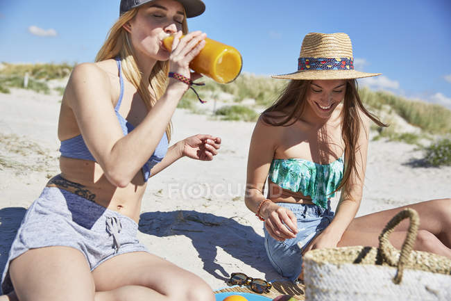 Two female friends drinking juice on the beach — Stock Photo
