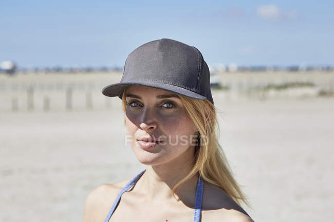 Happy young woman wearing baseball cap on the beach — one person ... 96fea9c64d5