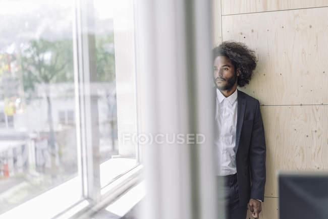 Молодий підприємець стоячи за вікном, думаючи, що — стокове фото
