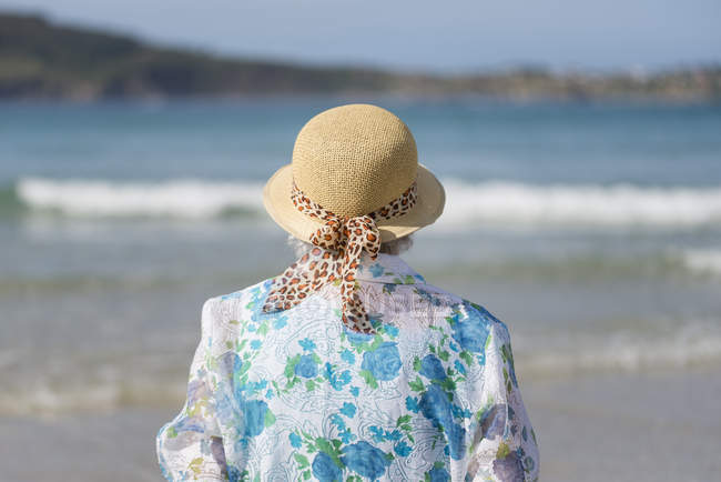 Back view of senior woman wearing straw hat on the beach looking at distance — Stock Photo