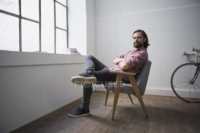 Uomo che si siede nella sedia con braccia incrociate a casa — Foto stock