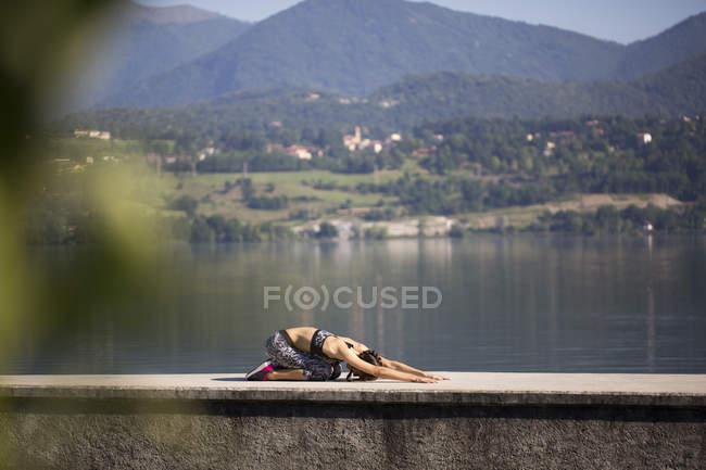 Молодая женщина делает упражнения на озере — стоковое фото