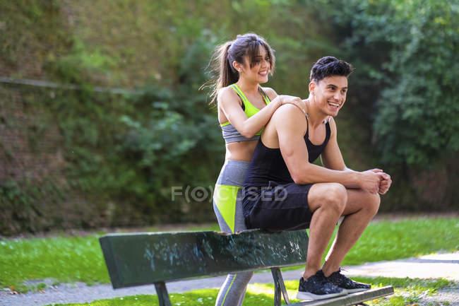 Sonriente deportista masajeando novio en banco - foto de stock