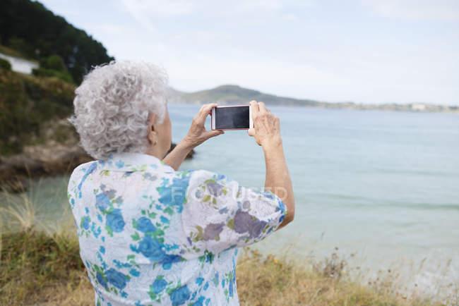 Visão traseira da mulher sênior tirando fotos do mar com smartphone — Fotografia de Stock