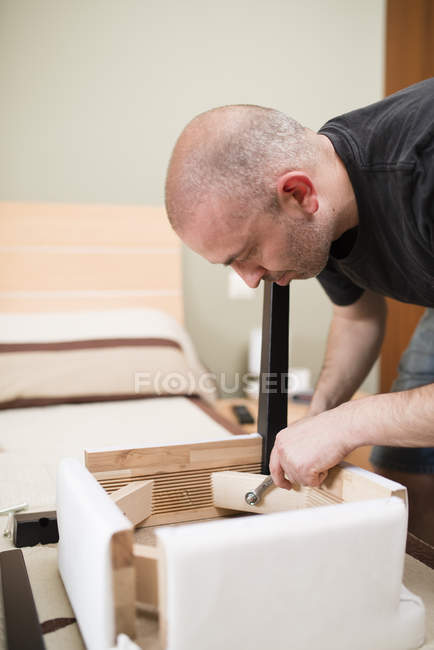 Man assembling furniture at home with screwdriver — Stock Photo