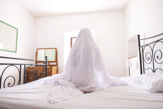 Rear view of woman with bed sheet sitting on bed in room — Stock Photo