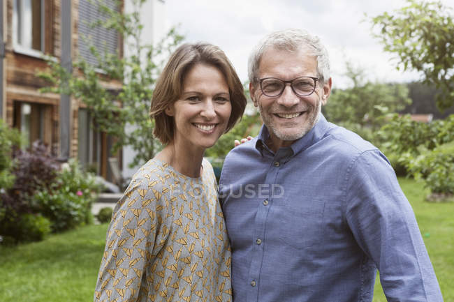 Portrait of smiling mature couple in garden — Stock Photo