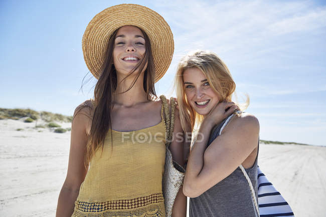 Two smiling female friends on the beach — Stock Photo