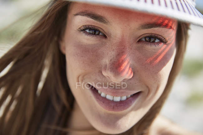 Smiling young woman in straw hat on the beach — Stock Photo