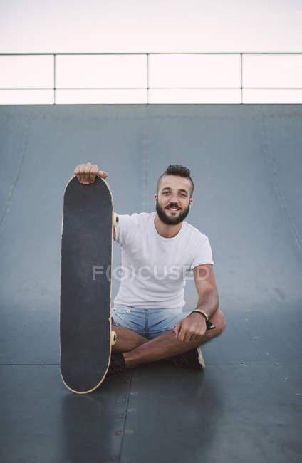 Skateboarder auf Rampe im Skatepark mit Skateboard sitzt lächelnd — Stockfoto
