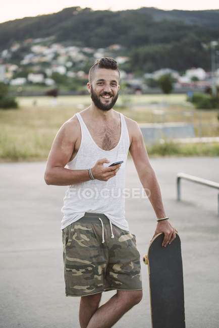Portrait of smiling man with skateboard and smartphone standing in skatepark — Stock Photo
