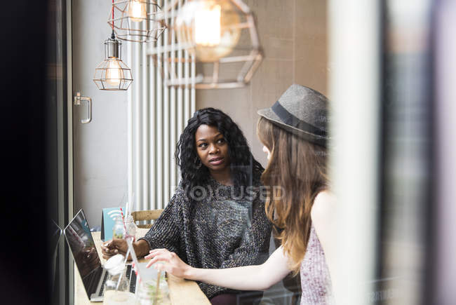 Two friends having a meeting cafe, using laptop — Stock Photo