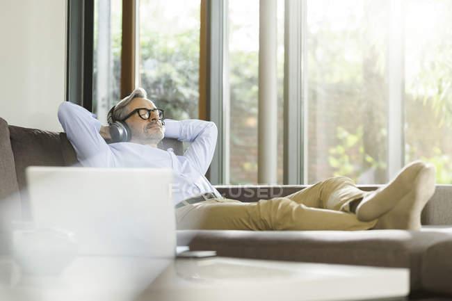 Uomo che si rilassa sul divano ascoltando musica con cuffie — Foto stock