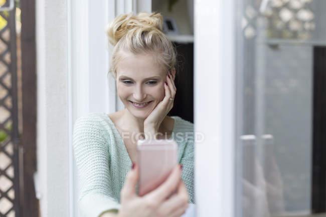 Blondine sitzt mit Handy an Terrassentür — Stockfoto