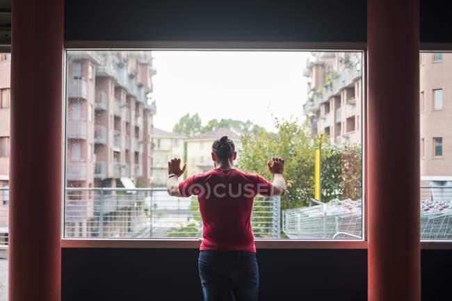 Visão traseira do homem olhando através da janela — Fotografia de Stock
