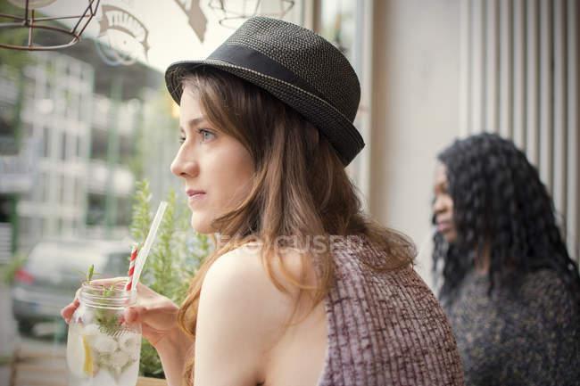 Amici seduti in un caffè, guardando fuori della finestra — Foto stock