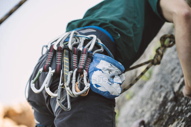 Close-up of magnesium bag and climbing carbines of man climbing rock wall — Stock Photo