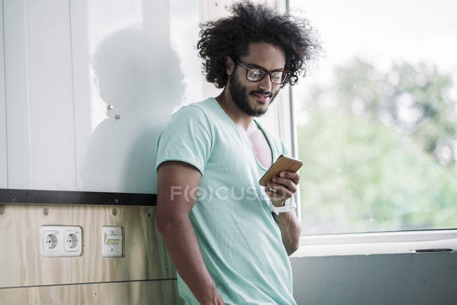 Man in office using smart phone — Stock Photo