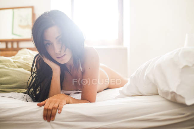 Young attractive woman in lingerie lying on bed, against sunlight — Stock Photo