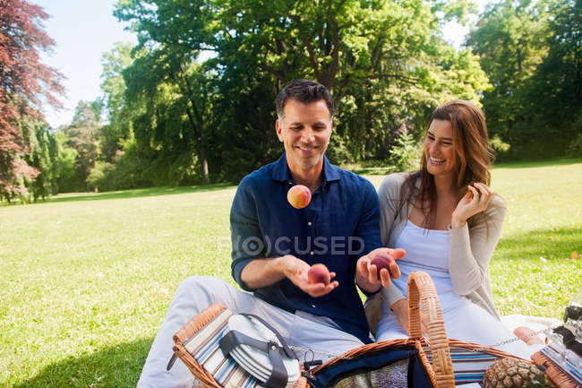 Couple having fun with peaches at park — Stock Photo