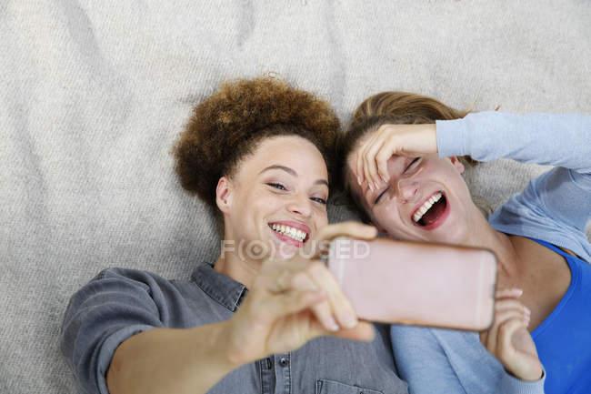 Due giovani donne felici che si fanno selfie sulla coperta — Foto stock