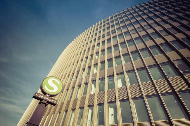 Germania, Berlino, torre degli uffici di Ernst e Young con cartello della stazione S-Bahn Friedrichstrasse in primo piano — Foto stock