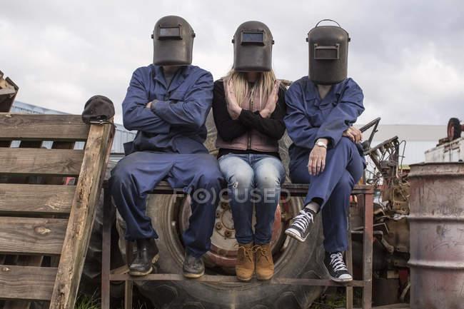 Três pessoas usando capacetes de solda sentados ao ar livre — Fotografia de Stock