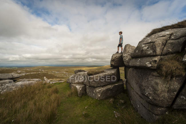 Garçon debout sur la formation rocheuse Rough Tor — Photo de stock