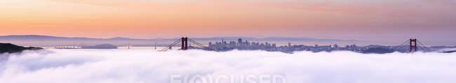 EE.UU., California, San Francisco skyline y Golden Gate Bridge en la niebla - foto de stock