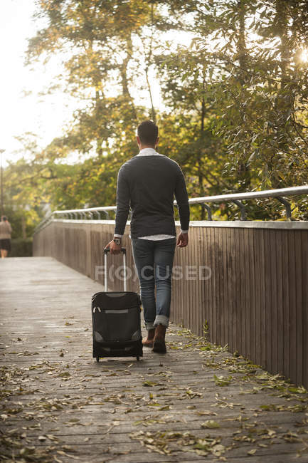 Young man walking with his wheeled luggage on a footbridge — Stock Photo