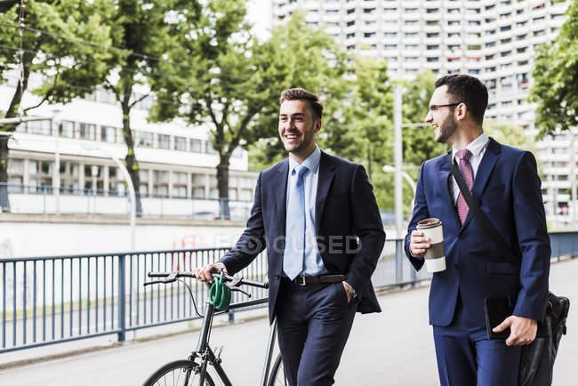 Hommes d'affaires marchant à vélo dans la ville et parlant — Photo de stock