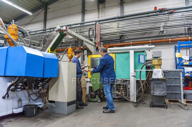 Gerente e trabalhador examinando produtos na fábrica de gesso — Fotografia de Stock
