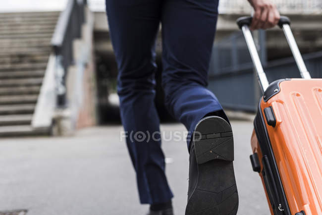 Cropped image of businessman on business trip running with wheeled luggage — Stock Photo