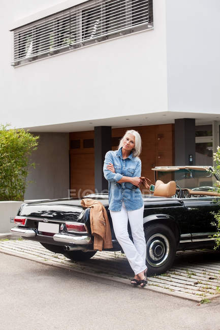 Mature woman leaning on convertible car in front of her one-family house — Stock Photo