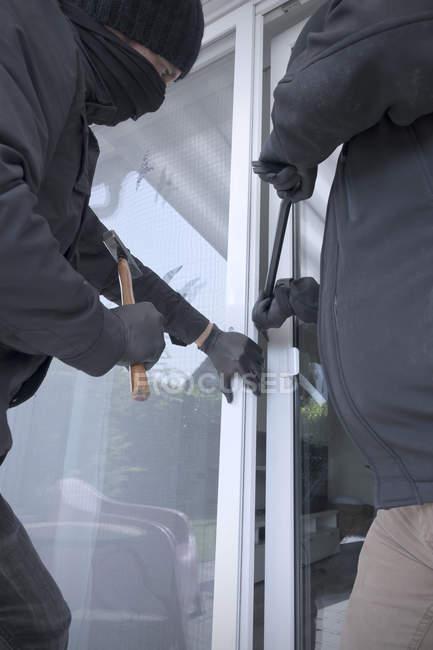 Dos ladrones que abren la puerta de la terraza de la casa con martillo y palanca - foto de stock
