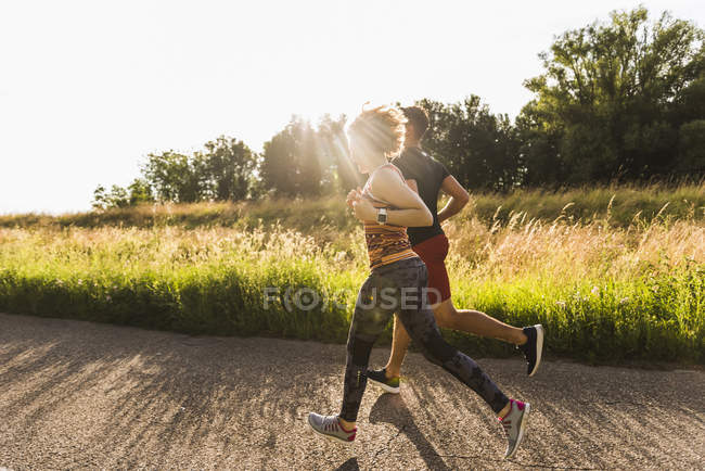 Young couple running on road in countryside — Stock Photo
