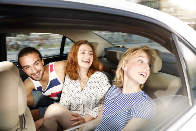 Amici seduti in taxi sul sedile posteriore — Foto stock