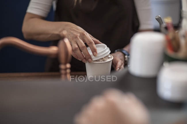 Barista closing lid of disposable coffee cup — Stock Photo