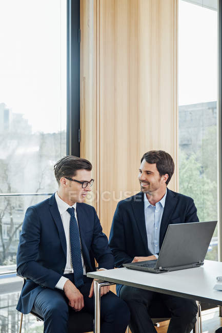 Two businessmen with laptop talking in office — Stock Photo