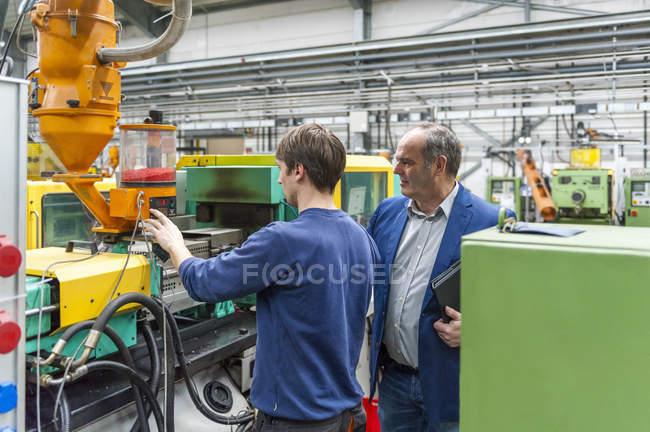 Двое мужчин регулируют машины на заводе пластмасс — стоковое фото