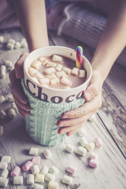 Руки на горячий шоколад с зефиром, чашка теплее — стоковое фото
