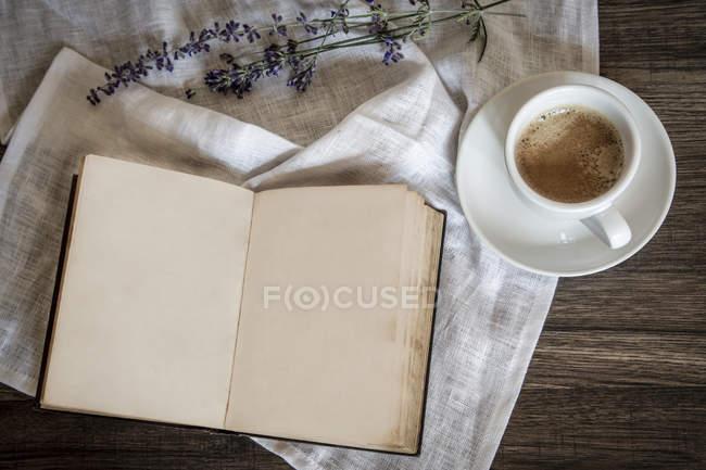 Натюрморт зі старої книги, чашку кави, лаванди та тканини — стокове фото