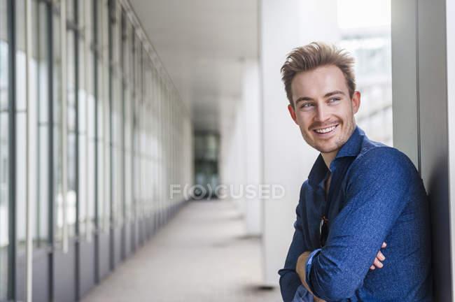 Portrait de jeune homme d'affaires détendu aux bras croisés — Photo de stock