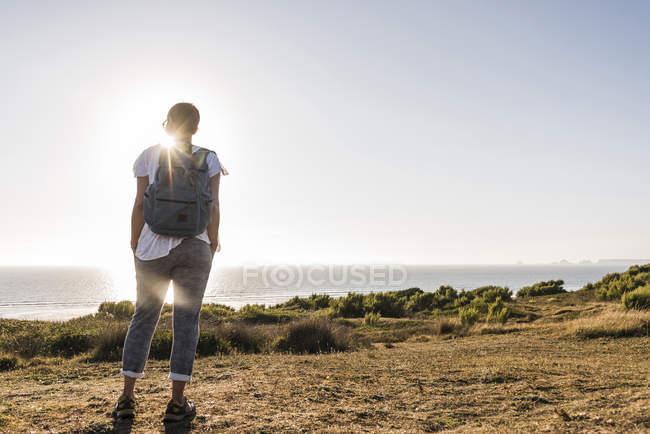 Жінка, стоячи на пагорбі над морем на заході сонця — стокове фото
